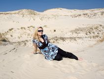Blond woman on sand dune royalty free stock images
