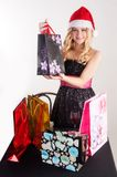 Blond woman in santa hat with shopping bags Stock Image
