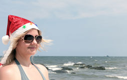Blond woman in Santa hat on tropical beach Royalty Free Stock Photo