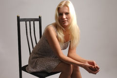 Blond woman sat on chair Stock Photos