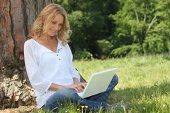 Blond woman sat by tree Stock Photos