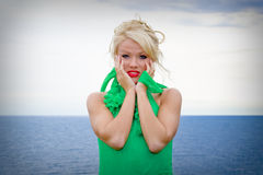 Blond woman by the sea. A beautiful blond model in green dress posing on the backdrop of the blue sea Royalty Free Stock Photography