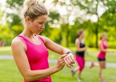 Blond woman setting her timer before jogging Royalty Free Stock Image