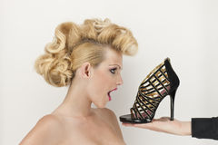Blond woman with shoe stock photos