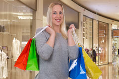 Blond woman with shopping bags in a shopping mall Royalty Free Stock Image