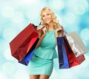 Blond woman with shopping bags. Smiling young blond woman with shopping bags over blurred background Royalty Free Stock Image