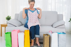 Blond woman with shopping bags trying out a top Royalty Free Stock Photography
