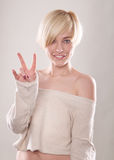 The blond woman with short hair and a beautiful smile with the index finger  isolated Royalty Free Stock Photo