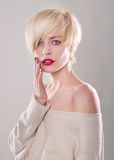 The blond woman with short hair  touches the lips Stock Photo