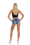 Blond Woman In Shorts And Sneakers Rear View Stock Photo