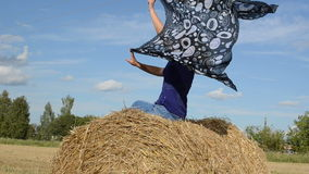 Blond woman sit straw bale field hold headscarf scarf move wind stock video
