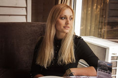blond woman sits in cafe and waits for her friend Royalty Free Stock Image
