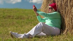 Blond woman sits on green grass near haystack and makes photos on his smartphone stock footage