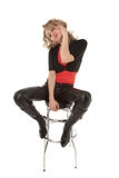Blond woman sitting on a bar chair. And looking to the camera Royalty Free Stock Image