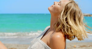 Blond Woman Sitting on Beach in front of Ocean stock footage