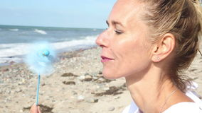 Blond woman sitting on the beach with a pinwheel stock video footage