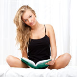 Blond woman sitting on bed and reading book Stock Photography