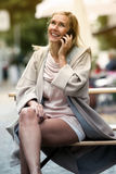 Blond woman sitting on bench and talking on phone Stock Photography