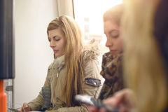 Blond woman sitting on crowded train or bus. Single blond women in gray winter coat sitting inside crowded commuter train or bus in front of window Stock Images