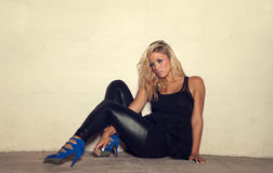Blond woman sitting down on flloor. Fashion concept image of beautiful club party girl sitting on sidewalk on a hot summers night. Image cross processed Royalty Free Stock Photo