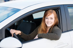 Blond woman. Sitting and driving in her car stock photography
