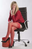Blond woman sitting in an executive black chair Stock Photos