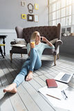 Blond woman sitting on floor and talking per phone Royalty Free Stock Images
