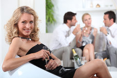 Blond woman sitting holding champagne Royalty Free Stock Photo