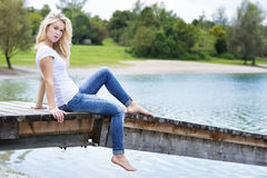 Blond woman sitting on a jetty Stock Photography