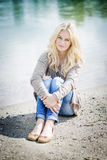 Blond woman sitting at lake Royalty Free Stock Image