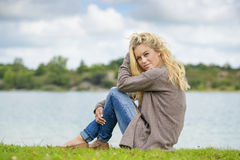 Blond woman sitting at lake Royalty Free Stock Images