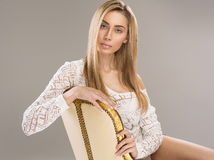 Blond woman. Sitting on luxury chair with ornament Stock Photography