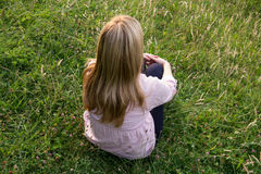 Blond woman sitting on meadow Royalty Free Stock Photo