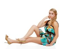 Blond woman sitting in a summer dress Stock Photography