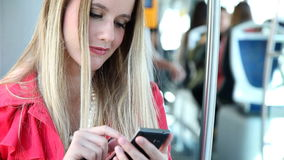 Blond woman sitting in tram, typing on phone stock footage