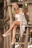 Blond woman sitting in a tree house Royalty Free Stock Photos