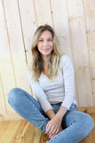Blond woman sitting on wooden floor Royalty Free Stock Photos
