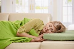 Blond woman sleeping on couch. Blond woman sleeping with blanket on couch in sunlit living room at home Royalty Free Stock Images