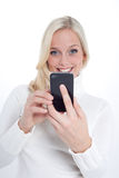 Blond woman with a smartphone Stock Images