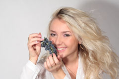 Blond woman smelling grapes royalty free stock images