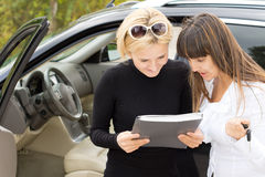 Blond woman smiling as she reads a contract. Blond women smiling as she reads a contract for the purchase of her new car with the saleslady who is holding the Stock Image