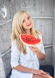 Blond woman smiling and holding a watermelon royalty free stock image