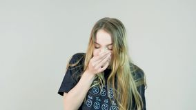 Blond woman sneezing on white background.  stock footage