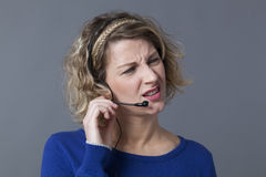 Blond woman squinting while responding to customer Stock Photo