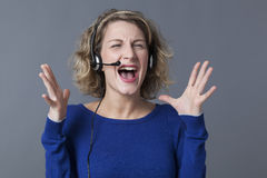 Blond woman squinting and shouting at customer Stock Image