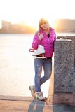 Blond woman standing with ice skates Royalty Free Stock Images