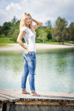 Blond woman standing on jetty Stock Photo