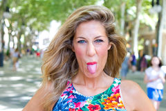 Blond woman sticking tongue out Royalty Free Stock Image