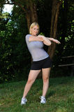 Blond woman stretching - fitness. Beautiful young blond woman stretching her arm (tricep) in the park before a run Stock Image