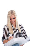 Blond Woman in Striped Shirt Writing in Binder. Smiling Blond Woman Wearing Striped Shirt Writing in Binder with Pen in Studio with White Background Royalty Free Stock Photography